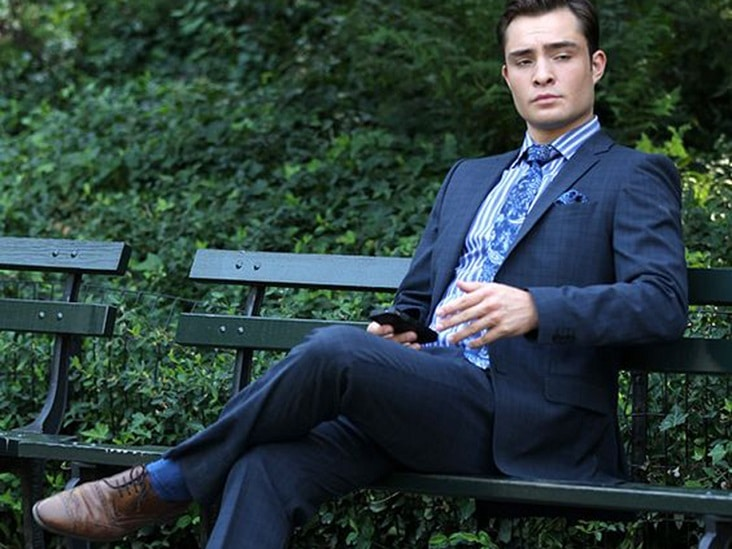 A man sitting on the bench wearing a suit and brown dress shoes holding a phone